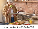 Small photo of Happy mature lady cooking at home
