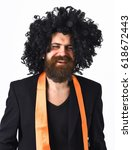 Small photo of Bearded man, long beard. Brutal caucasian smiling happy hipster with moustache have acid orange tie on suit and black curly afro wig isolated on white studio background
