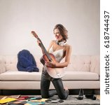 Small photo of Beautiful attractive woman playing a guitar like a rockstar. She is in a living room with vinyls all around.