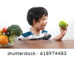 happy asian boy holding a green ... | Shutterstock . vector #618974483
