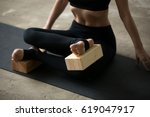 Small photo of Young sporty yogi woman practicing yoga concept, sitting in Agni stambhasana exercise, Fire Log, Ankle to Knee pose, using wooden block, working out, black mat background, legs close up