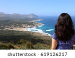 Small photo of view over the shoulder of a beautiful black-haired woman onto the coast of Mallorca and the beach of Cala Mesquida on a sunny day