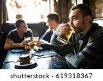 man drink beer in front of to... | Shutterstock . vector #619318367
