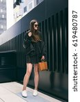 Small photo of perfect spring fashion outfit. fashionable woman wearing a oversized black bomber jacket and a black dress. fashion blogger posing on the street. accessorized with a brown handbag.