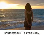 young woman stands on the beach.... | Shutterstock . vector #619569557