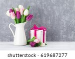 Small photo of Colorful tulips bouquet and gift box in front of stone wall with space for your greetings