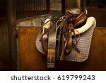 Stock photo cleaned quality horse tack in stable early morning light 619799243
