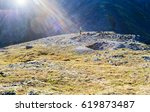 Small photo of A tourist girl, with a backpack and alpenstock, stands in the mountains at the pass in the rays of the sun.