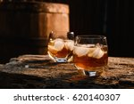 a glass of whiskey with ice on... | Shutterstock . vector #620140307