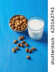 Small photo of Dairy alternative milk. Almond milk in a glass bottle and fresh nuts over a blue background, selective focus. Clean eating, dairy-free, vegan, vegetarian, allergy-friendly, healthy food concept.