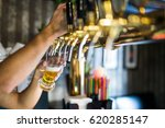 barman hand at beer tap pouring ...   Shutterstock . vector #620285147