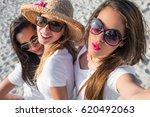 Small photo of Group of three beautiful young girls laughing and having fun on the beach on the sand with white t-shirts becoming selfies