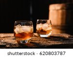 a glass of whiskey with ice on... | Shutterstock . vector #620803787