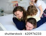Small photo of Morning in amicable family. Mum, daddy and two children have fun on a bed. All it is cheerful. All in pyjamas.