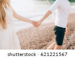 newlyweds hold hands on the sea.... | Shutterstock . vector #621221567
