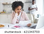 Small photo of Worried african american wife sitting at kitchen table, reading notification from bank, trying to pay gas and electricity bills online, while her husband standing with smartphone on background