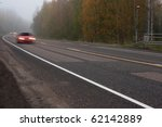 Dangerous mist on country road in forest with fast moving cars - stock photo