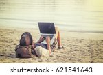 Small photo of Young woman using laptop computer on a beach. Freelance work concept
