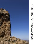 Small photo of Hikers Seem Dwarfed Next To The Enormous Volcanic Rock Roque Nublo (Rock in the Clouds), One Of The Highest Peaks On The Island Of Gran Canaria, Canary Islands, Spain. Vertical Establishing Shot.