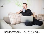 young man sitting on sofa with... | Shutterstock . vector #622149233