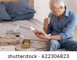 serious elderly man reading an... | Shutterstock . vector #622306823