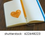 Small photo of Heart symbol with pencil on open blank notebook page. Love message romance concept. Lyrics loveletter book.