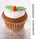 Small photo of ONE ICED CHRISTMAS CHOCOLATE SPONGE CUPCAKE DECORATED WITH FONDANT HOLLY LEAVES AND BERRIES,ON SILVER