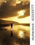 Small photo of Woman jumping in front of a beautiful sunset in Raglan, NZ.