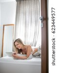Small photo of Beautiful young woman in bed, using her tablet computer first thing in the morning