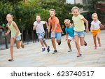 Small photo of spanish kids actively playing and running together on street on summer day