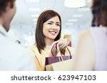 a shop assistant giving the... | Shutterstock . vector #623947103