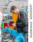 Small photo of Auckland, New Zealand - April 09, 2017: Man searching in many parts of thrown away as e-waste at EcoDay in New Lynn.