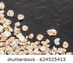 dry oatmeal on black concrete...   Shutterstock . vector #624525413