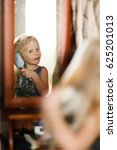 Small photo of Portrait of a girl who combs her hair in front of a mirror. Four-five-year-old child of European appearance. Concept of beauty, fashion, self-care, daily affairs, real life