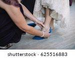 bride putting on blue shoes | Shutterstock . vector #625516883