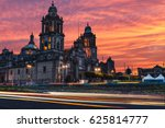 Small photo of The sun rises over the Mexico City Metropolitan Cathedral in the Zocalo Square of Mexico City, Mexico.