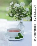 Small photo of Spiraea vanhouttei. Spiraea Flowers in a Glas Vase on a Table in a Garden. Spiraea Flowers on a White Tablecloth. Spiraea Flowers Bouquet and a White Cup of Tee.