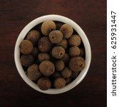 Small photo of allspice in wooden background