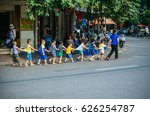 Small photo of Hanoi, Vietnam - 8 October 2016: A bunch of kids holding each other cloth and crossing the road together at the most bustling street where motorbikes, cars, bicycle all coming from all directions.