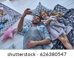 Capturing bright moments together. Top view of cheerful father and his little daughter taking selfie while lying on the floor at home together