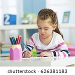 little girl drawing on a paper. | Shutterstock . vector #626381183