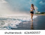 Stock photo active sporty woman run along ocean surf by water pool to keep fit and health sunset black sand 626400557