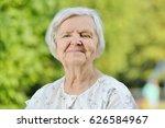senior woman smiling in park. | Shutterstock . vector #626584967