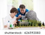 father and son work on model... | Shutterstock . vector #626592083
