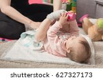 mother changing diapers of a... | Shutterstock . vector #627327173