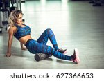Small photo of Attractive female doing foam roller exercise and posing in modern bright fitness center. Toned image.