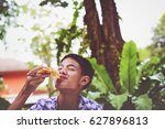 Small photo of Happy teenage boy ,young man enjoin eatting pizza in the park