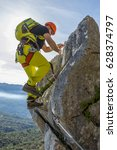 Small photo of Male alpinist in special outfit climbing rock on background of summit and sky