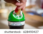 Man Putting Used Batteries Int...