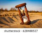 old hourglass on sand in desert | Shutterstock . vector #628488527